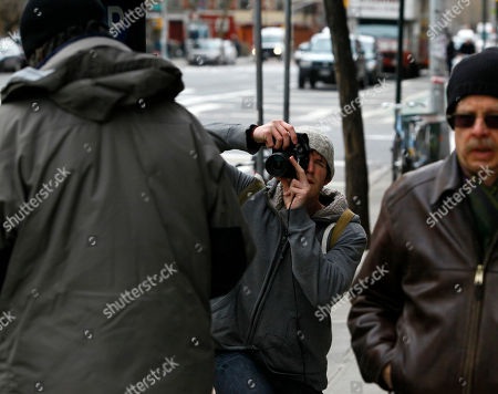 """Brandon Stanton Photographer Brandon Stanton, center, photographs a man on a New York City sidewalk for his project entitled """"Humans of New York."""" The photos go on his website, at humansofnewyork.com, and are linked to the neighborhoods in which they were taken"""