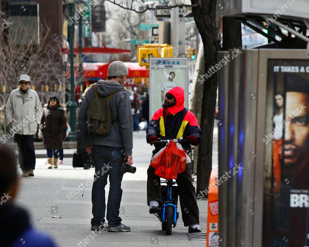 """Brandon Stanton Photographer Brandon Stanton, left, speaks to a bicyclist on a New York City street while working his project entitled """"Humans of New York."""" Stanton's photos go on his website, at humansofnewyork.com, and are linked to the neighborhoods in which they were taken"""