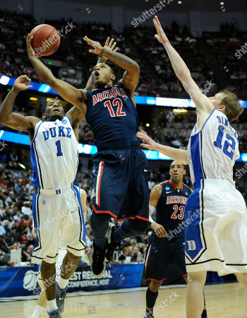 Lamont Jones;Kyrie Irving;Kyle Singler Arizona's Lamont Jones (12) drives between Duke's Kyle Singler (12) and Kyrie Irving (1) during the second half of a West regional semifinal game in the NCAA college basketball tournament, in Anaheim, Calif. Arizona defeated Duke 93-77