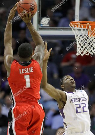 Travis Leslie, Justin Holiday Georgia guard Travis Leslie (1) shoots as Washington forward Justin Holiday (22) defends in the first half of an East Regional NCAA tournament second-round college basketball game, in Charlotte, N.C