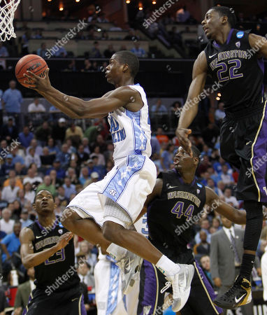 Stock Image of North Carolina guard Patrick Crouch (30) goes to the basket as Washington forward Justin Holiday (22) defends in the first half of an East Regional NCAA tournament third-round college basketball game, in Charlotte, N.C. Washington guard C.J. Wilcox (23) and Washington forward Darnell Gant (44) look on