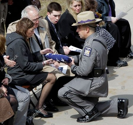 Bridgett Hastings, partner of New York State Trooper Kevin Dobson, accepts the flag during his funeral at the Eastern Hills Wesleyan Church in Amherst, N.Y., . Dobson was was hit by a car and killed while writing a traffic ticket