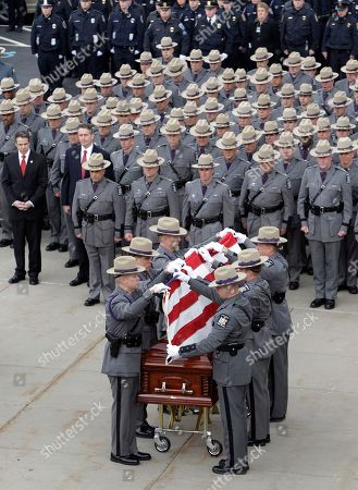 New York State Troopers fold the flag covering the casket of New York State Trooper Kevin Dobson during his funeral at the Eastern Hills Wesleyan Church in Amherst, N.Y., . Dobson was was hit by a car and killed while writing a traffic ticket