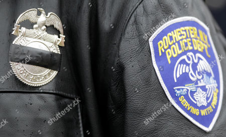 A Rochester police officer wears a mourning ribbon over his badge while attending the funeral of New York State Trooper Kevin Dobson at the Eastern Hills Wesleyan Church in Amherst, N.Y., . Dobson was was hit by a car and killed while writing a traffic ticket