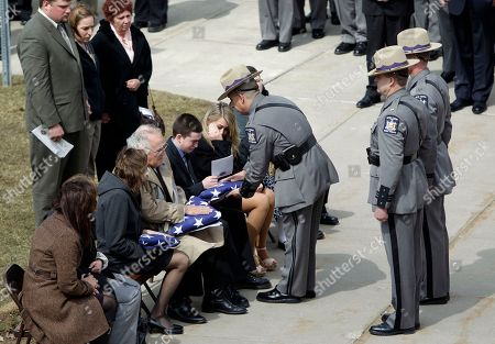 Kevin Dobson Jr., son of New York State Trooper Kevin Dobson, accepts the flag during his father's funeral at the Eastern Hills Wesleyan Church in Amherst, N.Y., . Dobson was hit by a car and killed while writing a traffic ticket