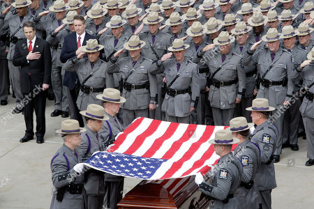 New York State Troopers fold the flag during the funeral of New York State Trooper Kevin Dobson at the Eastern Hills Wesleyan Church in Amherst, N.Y., . Dobson was was hit by a car and killed while writing a traffic ticket