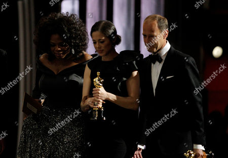 "Oprah Winfrey, Charles Ferguson, Audrey Mars From left, presenter Oprah Winfrey leaves the stage with Audrey Marrs and Charles Ferguson, winners of the Oscar for best documentary feature for ""Inside Job"" at the 83rd Academy Awards, in the Hollywood section of Los Angeles"