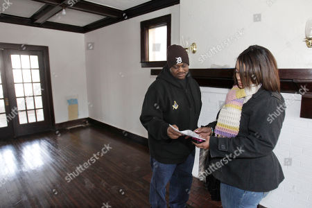 Stock Image of William Booker-Riggs, Nancy Williams Real estate agent Nancy Williams, right, shows Detroit police officer William Booker-Riggs some information inside a house in the Boston Edison section of Detroit, . The city hopes its renovated homes incentive will lure police officers to move into and stabilize Detroit neighborhoods