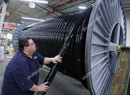 Jim Bell helps spool a high pressure hose used in hydraulics applications such as the oil and gas industry, at Eaton Corp., in Aurora, Ohio. Eaton Corp.'s fourth-quarter net income surged 33 percent, and the diversified industrial manufacturer boosted its dividend and announced a 2-for-1 stock split Thursday