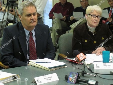 Todd Thompson, left, an attorney representing former University of Kansas Athletics Director Lew Perkins, awaits the Kansas Governmental Ethics Commission's discussion of an agreement he signed with Judy Moler, right, the commission's general counsel, to settle an ethics case involving Perkins, in Topeka, Kan. Perkins agreed to pay a $4,000 fine but acknowledged no intentional wrongdoing