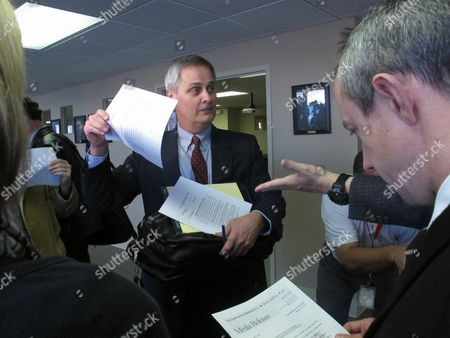 Todd Thompson, an attorney representing former University of Kansas Athletics Director Lew Perkins, hands out copies of a statement from Perkins about the resolution of an ethics complaint against him, in Topeka, Kan. Perkins agreed to pay a $4,000 fine to end the case, without acknowledging any intentional wrongdoing in accepting a gift of exercise equipment while working for the university