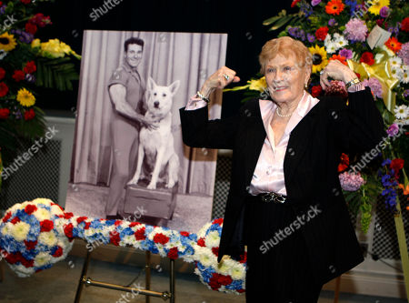 Stock Photo of Elaine LaLannne strikes a characteristic pose near a portrait of her late husband Jack LaLanne at a memorial service for guru of physical fitness in Los Angeles . LaLanne died Jan. 23 at the age of 96
