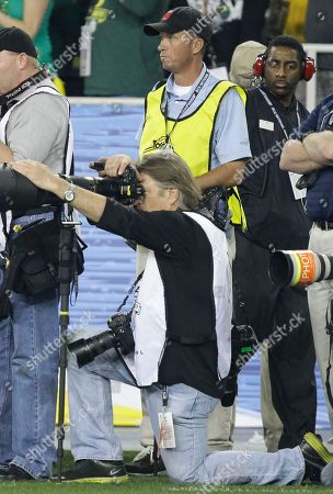 Phil Mickelson's caddie Jim Mackay, wearing yellow vest, stands behind Sports Illustrated photographer Robert Beck during the second half of the BCS National Championship NCAA college football game, in Glendale, Ariz. Mackay worked the sidelines as an assistant to Beck, lugging the award-winning lensman's equipment around the field as he captured the action of Auburn's thrilling 22-19 last-second victory