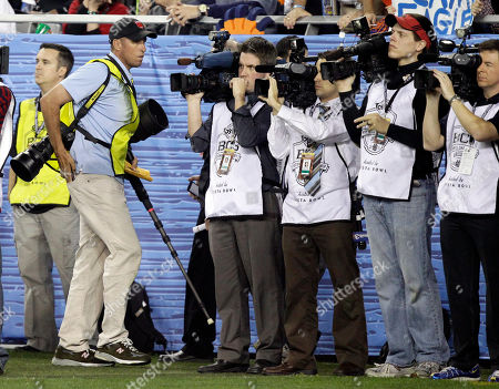 Phil Mickelson's caddie Jim Mackay, wearing yellow vest at left foreground, carries camera equipment during the second half of the BCS National Championship NCAA college football game, in Glendale, Ariz. Mackay worked the sidelines as an assistant to Sports Illustrated photographer Robert Beck, not shown, lugging the award-winning lensman's equipment around the field as he captured the action of Auburn's thrilling 22-19 last-second victory