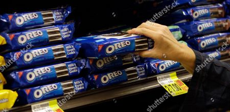 A shopper selects Oreo cookies at a Ralphs Fresh Fare supermarket in Los Angeles. Activist investor Bill Ackman is paying approximately $5.5 billion for a 7.5 percent stake in Mondelez International Inc., the maker of products, including Oreo cookies and Cadbury chocolate, according to reports