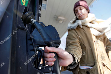 David Castro-Diephouse returns the nozzle to the pump after filling his car's tank with gas in Philadelphia, . Gasoline pump prices reached a 28-month high Wednesday even though oil and gas supplies in the U.S. continue to grow and demand for gas is weak