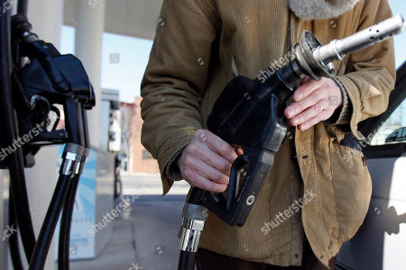 In this Feb. 16, 2011 photo, David Castro-Diephouse returns the nozzle to the pump after filling his car's tank with gas in Philadelphia. Oil prices rose above $104 per barrel, as traders continued to focus on a series of international crises that will drive world supply and demand this year
