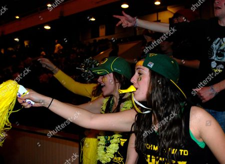 University of Oregon students Ashley Taylor of Sacramento, Calif., right, and Nichole Musket of Missoula, Mont., cheer on the Ducks in the BCS championship game Monday night while watching on big-screen TVs in McArthur Court in Eugene, Ore. Duck fans were disappointed as Oregon fell to Auburn 22-19