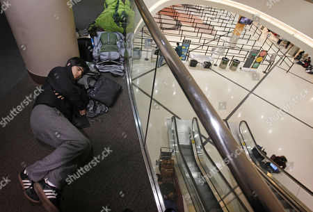 Samuel Wilson Samuel Wilson, of South Korea, left, sleeps along an upstairs hallway as the security checkpoint below stands vacant as a severe storm canceled most flights at Atlanta's Hartsfield-Jackson International Airport, in Atlanta