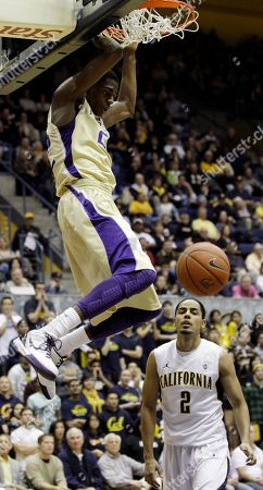 Justin Holiday, Jorge Gutierrez Washington 's Justin Holiday (22) dunks as California 's Jorge Gutierrez (2) looks on during the first half of an NCAA college basketball game in Berkeley, Calif