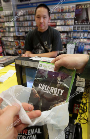 """Joe Chen, 18, watches as his pre-ordered copy of the new """"Call of Duty: Black Ops,"""" video game is placed in a bag after it went on sale in Sacramento, Calif. One of the most anticipated game introductions of the year, Call of Duty: Black Ops, from Activision went on sale at midnight Tuesday morning"""
