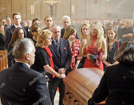 Martha De Laurnetiis stands behind her husband's casket as her daughter Dina dabs at her face, left, with other daughter Carolyna at right, at the funeral of Italian filmmaker Dino De Laurentiis, at the Cathedral of Our Lady of the Angels in Los Angeles . California Gov. Arnold Schwarzenegger and his wife Maria Shriver are at left rear