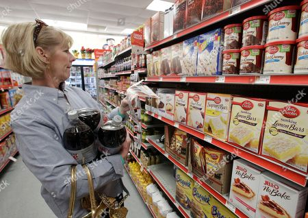 Sharon Sexton of Waco, Texas, attempts to locate a baking item to match a coupon she clipped from her local newspaper at the Family Dollar store, in Waco, Texas. Family Dollar Stores Inc.'s fiscal second-quarter net income rose 10 percent, helped by better traffic and a modest improvement in the value of the average customer transaction