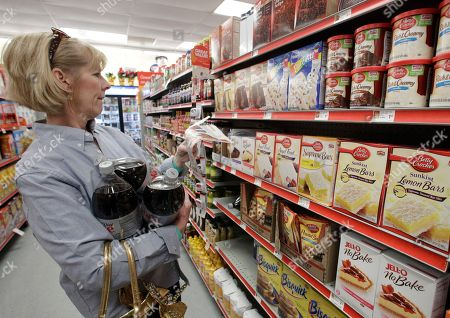 In this Dec.14, 2010 photo, Sharon Sexton of Waco, Texas, attempts to locate a baking item to match a coupon she clipped from her local newspaper at the Family Dollar store, in Waco, Texas. Rising wholesale prices for food and energy are putting pressure on retailers to pass along the costs to customers, threatening to slow the global economy