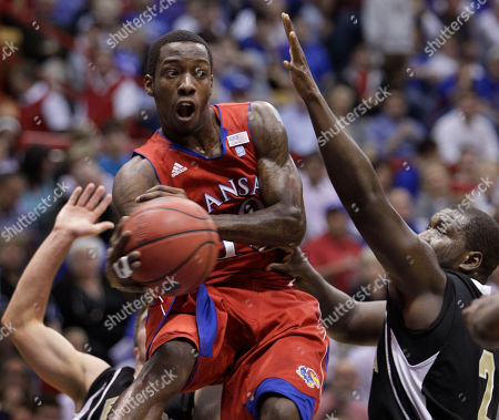 Stock Image of Tyshawn Taylor, Michael Tyler Kansas guard Tyshawn Taylor (10) passes around Emporia State forward Michael Tyler (22) during the first half of an exhibition college basketball game in Lawrence, Kan., . Kansas defeated Emporia State 90-59