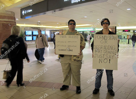 Patricia Stone and her husband John Richards of Chandler hold signs at Phoenix Sky Harbor International Airport to protest body scanners and thorough pat-downs