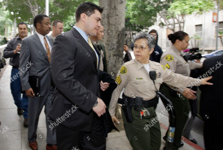 Security guard Alberto Alvarez, center, and his attorney Carl Douglas, left rear, they leave the preliminary hearing for Michael Jackson's doctor Conrad Murray, charged in the death of the singer, at Los Angeles Superior Court