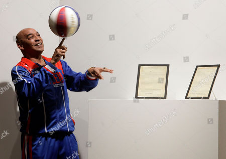 Curly Neal Former Harlem Globetrotters basketball player Curly Neal spins a ball on his finger tip prior to the bidding for the Naismith Rules, the original rules for basketball, framed at right, at Sotheby's in New York