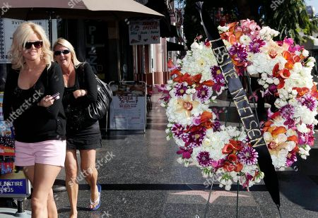 """Visiting tourists walk past flowers placed on the star for actor Leslie Nielsen on the Hollywood Walk of Fame in the Hollywood section of Los Angeles, . Nielsen, the dramatic lead in """"Forbidden Planet"""" and """"The Poseidon Adventure"""" and the bumbling detective Frank Drebin in """"The Naked Gun"""" comedies, died on Sunday in Fort Lauderdale, Fla. He was 84"""