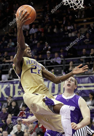 Ryan Nicholas, Justin Holiday Washington's Justin Holiday (22) goes to the basket in front of Portland's Ryan Nicholas in the second half of an NCAA college basketball game, in Seattle. Washington won 94-72
