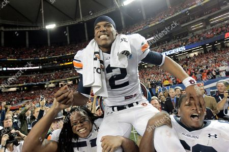 Auburn quarterback Cameron Newton (2) gets hoisted by teammates Mike Berry (66) and Byron Isom (57) at the end of the Southeastern Conference Championship NCAA college football game against South Carolina at the Georgia Dome in Atlanta, . Auburn won 56-17
