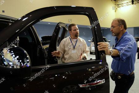 Jeff Walker, James Duggan Jeff Walker of Detroit, Mich., left, shows a 2011 GMC Sierra to James Duggan of Miami Beach, Fla., right, during the South Florida International Auto Show in Miami Beach, Fla