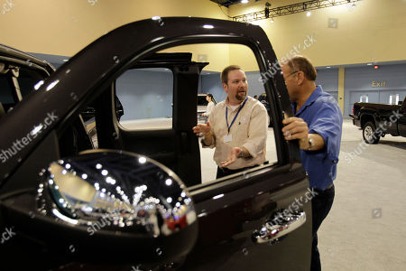 Jeff Walker, James Duggan Jeff Walker of Detroit, Mi., left, shows a 2011 GMC Sierra to James Duggan of Miami Beach, Fla., right, during the South Florida International Auto Show in Miami Beach, Fla