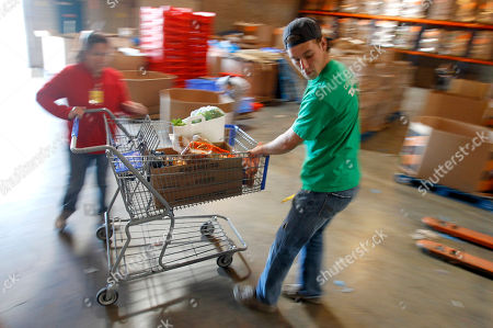 Stock Image of Eric Hudspeth, Veronica Hernandez Food bank volunteers Eric Hudspeth, right, and Veronica Hernandez load up a grocery cart full of food for pickup as hundreds lined up to get their Thanksgiving dinner food at the St. Mary's Food Bank Alliance, in Phoenix