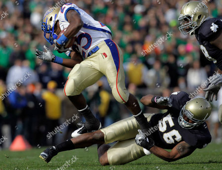 Stock Picture of Kerry Neal, JaTerian Douglas Tulsa running back JaTerian Douglas is tackled by Notre Dame linebacker Kerry Neal (56) during the first half of an NCAA college football game, in South Bend, Ind
