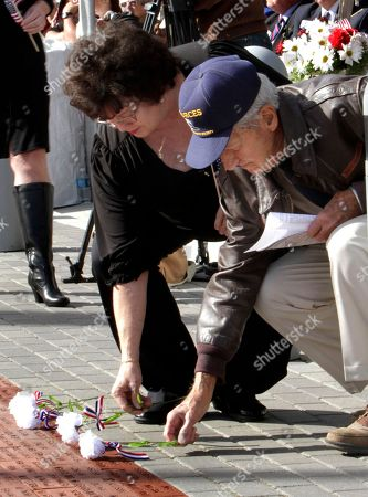 Linda Hogan, left, and Joseph Manos, right, place flowers on bricks with the names of their loved ones at the Veterans Memorial Plaza at the Sacramento Veterans Affairs Medical Center in Rancho Cordova, Calif., . Brown honored her husband, James, a Viet Nam veteran, and Manos honored his brother Nicholas, who was killed during World War II. Manos was a B-17 bomber crewman in World War !! and retired from the Air Force after 20 years