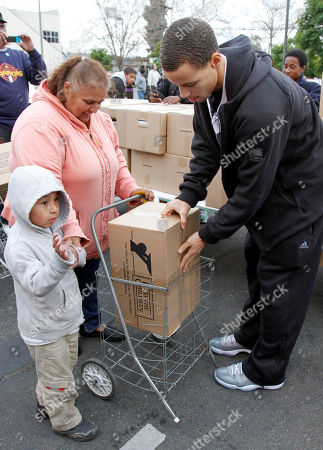 Stock Image of Monta Ellis, Stephen Curry Golden State Warriors' Stephen Curry, right, loads the basket of a needy family with food, in Oakland, Calif. Curry and teammate Monta Ellis are teaming with international hunger relief organization Feed The Children to provide 800 local families with boxes of food and personal care items. With financial backing from Curry & Ellis, Feed The Children brought two semi tractor-trailers full of food and other essentials to Allen Temple, where each of the pre-identified families received their items