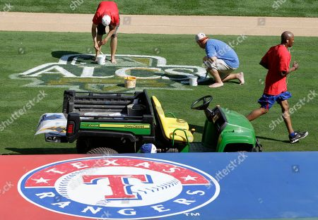 Gary Pettis Texas Rangers grounds crew employees Stephen Lord, top left, and Taylor Atzert, center, paint the AL championship series logo as first base coach Gary Pettis, right, jogs past, in Arlington, Texzas. The Rangers will host the New York Yankees on Friday and Saturday in the first two games of the series