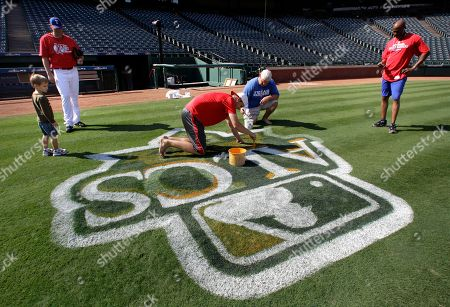 Colby Lewis, Cade Lewis, Taylor Atzert, Stephen Lord Texas Rangers starting pitcher Colby Lewis, second left, his 3 1/2-year-old son Cade, and first base coach Gary Pettis, right rear, look on as grounds crew personnel Stephen Lord, center left, and Taylor Atzert paint the ALCS logo on the first base line, in Arlington, Texas. The Rangers host the New York Yankees in Game 1 of baseball's American League Championship Series on Friday