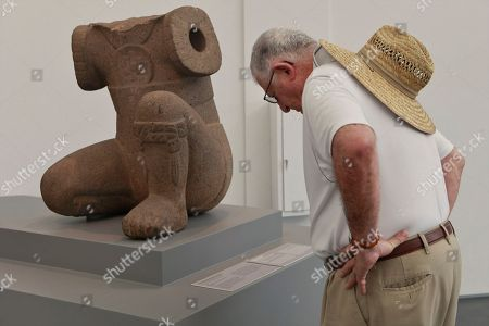 """On, a museum patron looks at Monument 34, a basalt half-kneeling figure from the 1400-1000 BC period is part of The """"Olmec: Colossal Masterworks of Ancient Mexico,"""" installation is on view at the newly inaugurated Lynda and Stewart Resnick Exhibition Pavilion at the Los Angeles County Museum of Art"""
