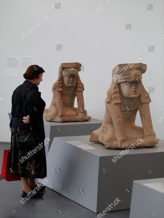 """On, a museum visitor looks at two seated figures wearing a cape, from the 900-400 BC period, part of The """"Olmec: Colossal Masterworks of Ancient Mexico,"""" installation on view at the newly inaugurated Lynda and Stewart Resnick Exhibition Pavilion at the Los Angeles County Museum of Art"""