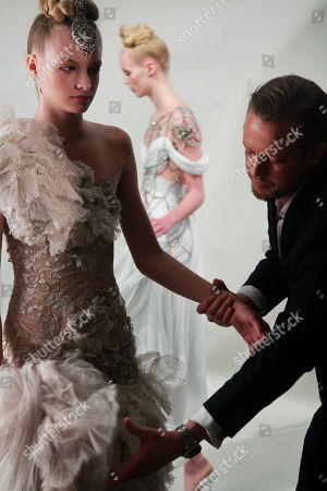 Stock Photo of Edward Chapman, right, CEO of Marchesa, prepares a model for the presentation of the Marchesa Spring 2011 collection, during Fashion Week in New York
