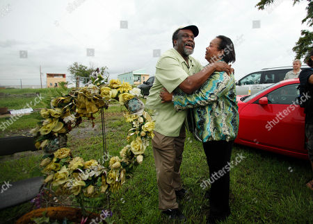 Hurricane Katrina survivor Robert Green, Sr., who lost his mother and granddaughter in the storm, hugs Veronica Henry after leading a second line parade through the Lower Ninth Ward on the fifth anniversary of Hurricane Katrina in New Orleans