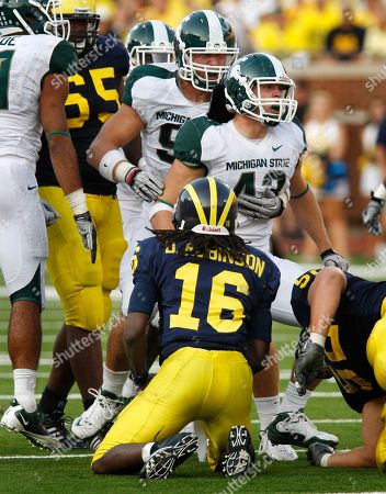 Michigan quarterback Denard Robinson (16) looks towards Michigan State tackle Blake Treadwell, background, and linebacker Eric Gordon (43) after Gordon's tackle on Robinson in the third quarter of a college football game in Ann Arbor, Mich