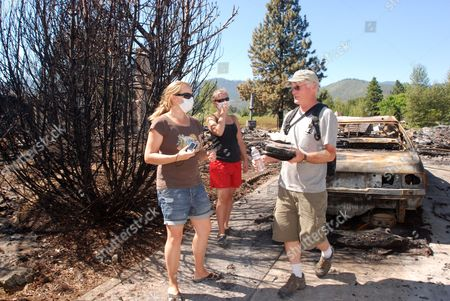 Gary Jones, his daughter, Lisa Jones, center, and her best friend, Lauren Jones, head home with a photo album and a paperback book, all they could salvage from the ruins of Lisa Jones' home in Ashland, Ore. The house was one of 11 destroyed Tuesday by a fast-moving wildfire. A homeless man has been arrested on charged he started the blaze