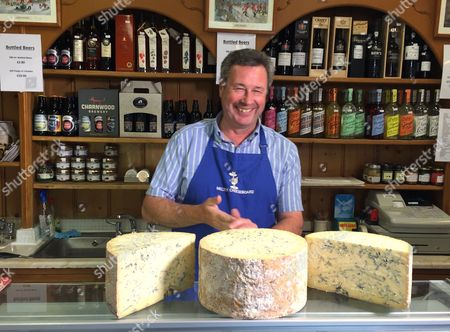On, Tim Brown, the owner of the the Melton Cheeseboard, weighs out some cheese in his shop in Melton Mowbray, England. The marker of distinction for British food, the same kind that ensures Champagne can only come from the French region of the same name, is granted by the European Union and is now at risk after Britain voted to leave the 28-country bloc. The certificates, of which there are 73 across Britain for goods like Stilton cheese and Melton Mowbray pork pies, not only help farmers earn more but also shape rural communities' identities